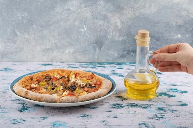 Vrouw hand met een glazen fles olie in de buurt van hete pizza op een marmeren achtergrond.