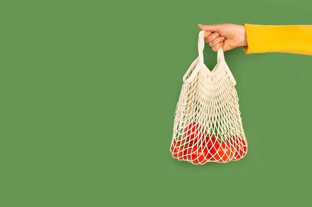 Vrouw hand met een katoenen mesh zak met rode tomaten op een green