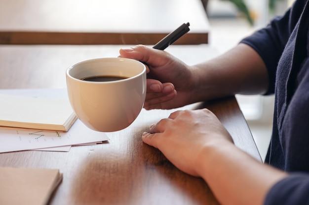 Vrouw hand met een kop warme koffie tijdens het werken aan bedrijfsdocument op houten tafel