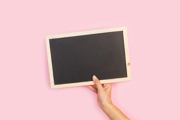 Vrouw hand met een leeg bord op een roze achtergrond