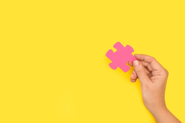 Vrouw hand met een roze puzzelstukje
