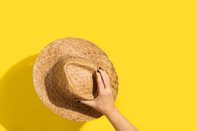 Vrouw hand met een strooien hoed op een gele achtergrond