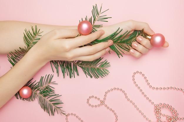 Vrouw hand met een tak met roze ballen