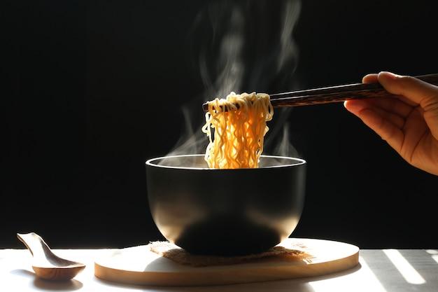 Vrouw hand met eetstokjes van instant noedels in cup met rook stijgt donker, natriumdieet hoog risico nierfalen, gezond eten concep