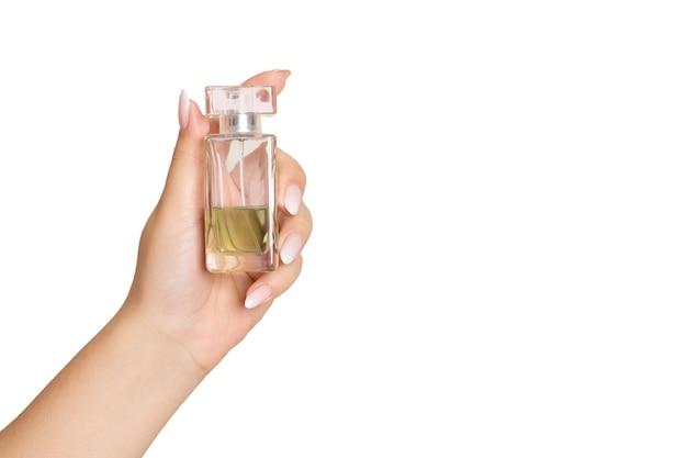 Vrouw hand met fles met toiletwater. geïsoleerd op wit, ruimte voor tekst