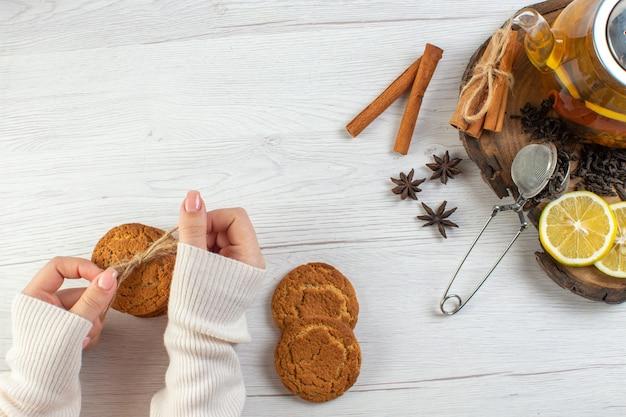 Vrouw hand met gestapelde koekjes zwarte thee met citroen