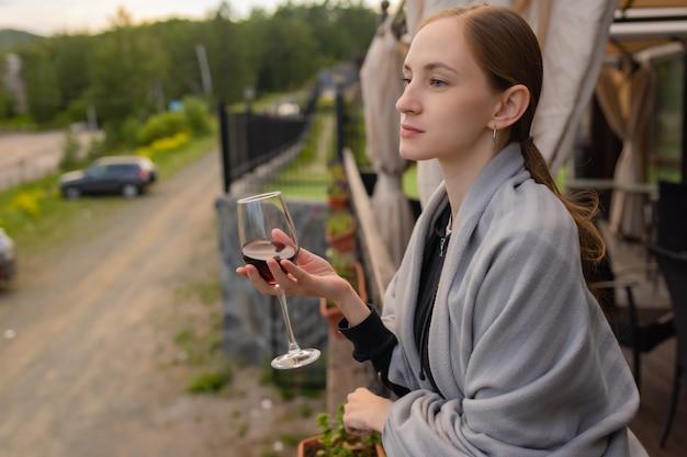 Vrouw hand met glas met wijn op onscherpe natuurlijke achtergrond.