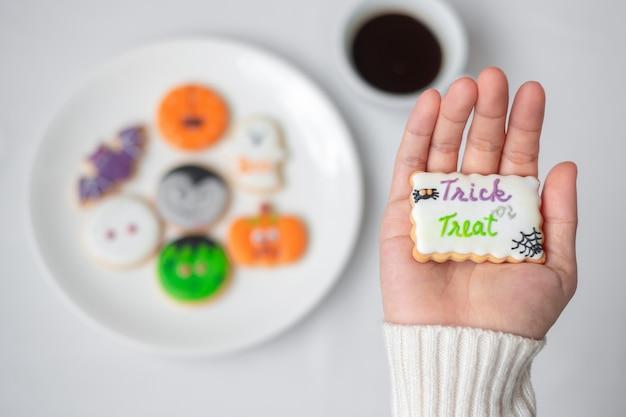Vrouw hand met grappige halloween cookie tijdens het drinken van koffie. fijne halloween-dag, trick or threat, hallo oktober, herfstherfst, traditioneel, feest- en vakantieconcept
