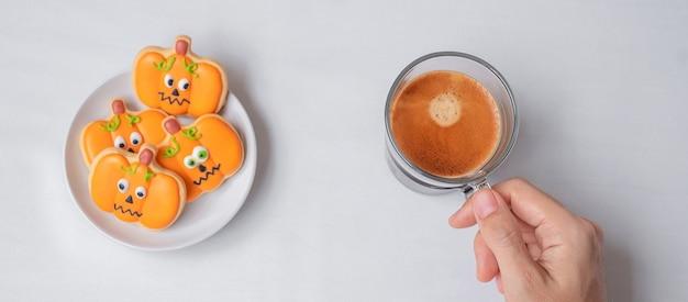 Vrouw hand met koffiekopje tijdens het eten van grappige halloween cookies. fijne halloween-dag, trick or threat, hallo oktober, herfstherfst, traditioneel, feest- en vakantieconcept
