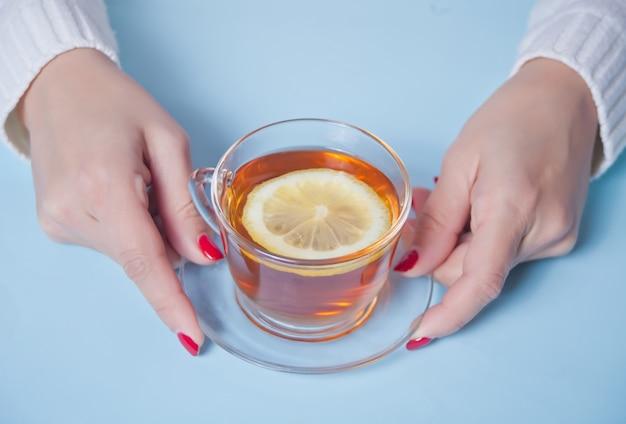 Vrouw hand met kopje thee met stuk citroen