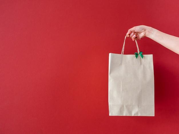 Vrouw hand met lege gerecyclede papieren zak versieren met groene strik op rode muur