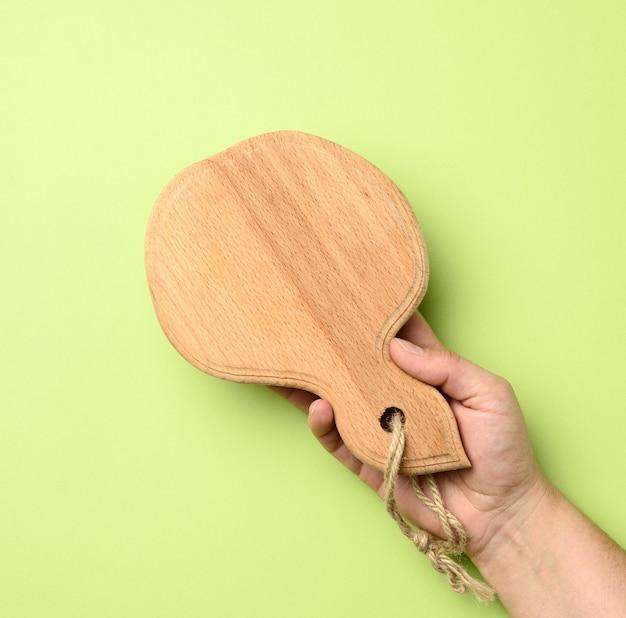 Vrouw hand met lege ronde houten plank in de hand