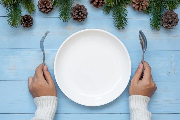 Vrouw hand met lepel en vork over lege plaat met decoratie van kerstmis