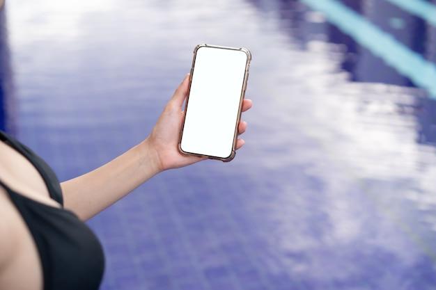 Vrouw hand met mobiele telefoon met leeg wit scherm mockup bij het zwembad.