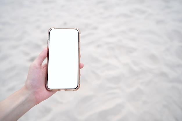 Vrouw hand met mobiele telefoon met leeg wit scherm mockup op het strand.