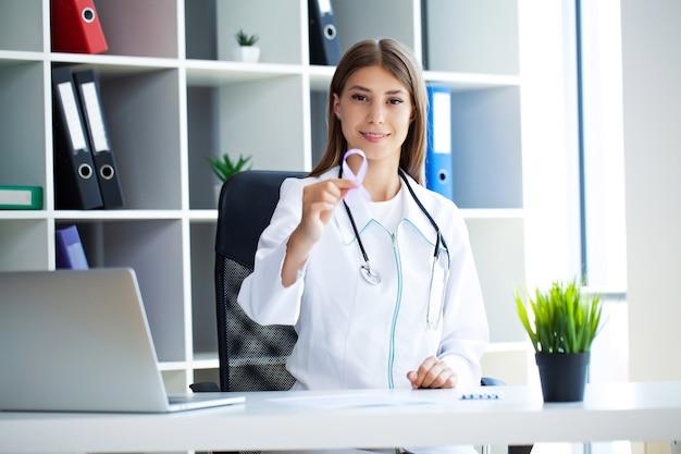 Vrouw hand met paarse strik, lupus lse of alzheimer bewustzijnssymbool.