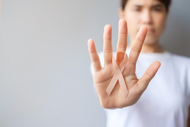 Vrouw hand met perzik lint voor september baarmoederkanker bewustzijn maand. gezondheidszorg en wereldkankerdag concept