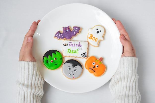 Vrouw hand met plaat van grappige halloween cookies. fijne halloween-dag, trick or threat, hallo oktober, herfstherfst, traditioneel, feest- en vakantieconcept