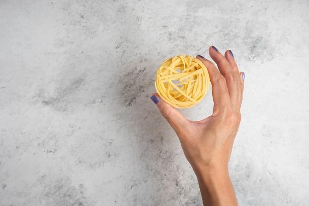 Vrouw hand met rauwe pasta nest op witte achtergrond.