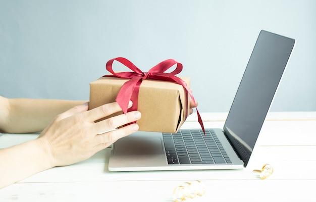 Vrouw hand met rode geschenkdoos over online winkelen concept.
