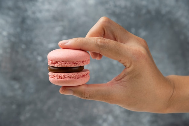 Vrouw hand met roze smakelijke macaron op marmeren oppervlak.