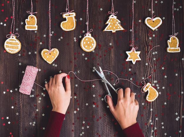 Vrouw hand met schaar bereidt peperkoek voor opknoping op kerstboom