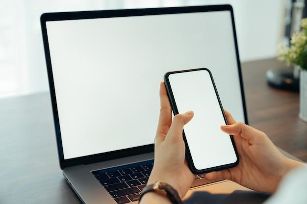 Vrouw hand met smartphone met lege kopie ruimte scherm voor uw advertentie. laptop op de tafel.