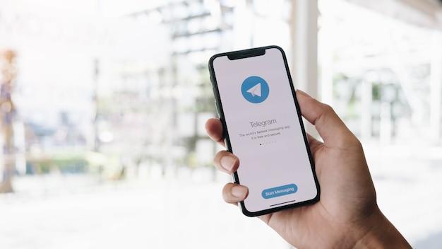 Vrouw hand met smartphone met telegram-app op het scherm.