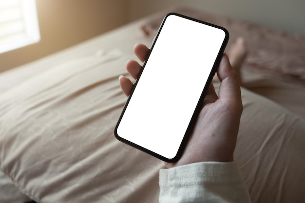 Vrouw hand met smartphone met vervaging bokeh. leeg scherm mobiele telefoon voor grafische weergave montage