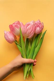 Vrouw hand met tedere roze tulpen onderaan pastel gele achtergrond. wenskaart voor vrouwendag. plat leggen. concept van internationale vrouwendag, moederdag, pasen. valentijnsdag liefdesdag