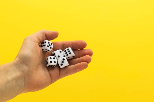 Vrouw hand met vijf dobbelstenen. speelkubus met getallen. items voor bordspellen. wazig gele achtergrond.