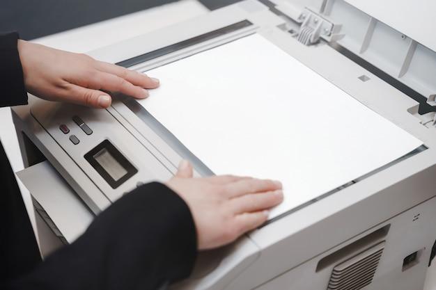 Vrouw hand met werkende kopieerapparaat