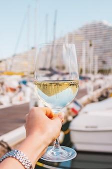 Vrouw hand met witte wijn champagne glas op een pier jachten gebouw en boten achtergrond