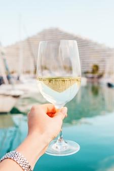 Vrouw hand met witte wijn champagne glas op jachten zeilboten bouwen achtergrond in frankrijk