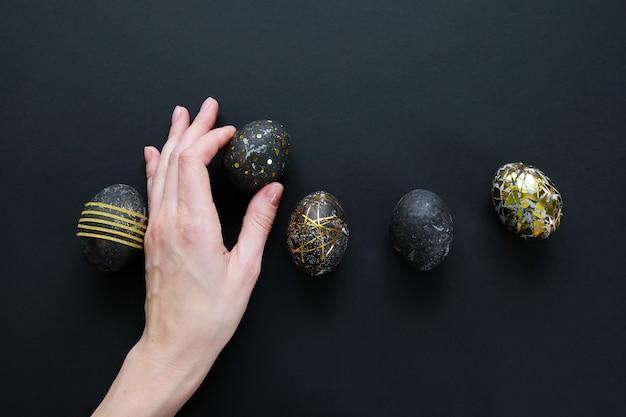 Vrouw hand met zwarte paaseieren met gouden patroon op zwarte achtergrond.