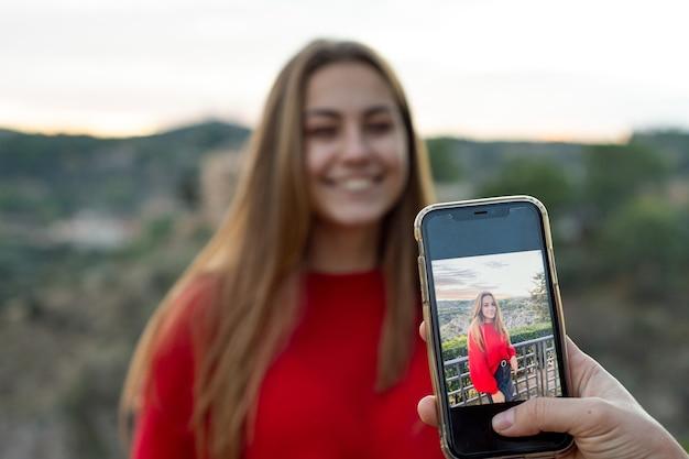 Vrouw hand nemen van een foto van een meisje in de stad.