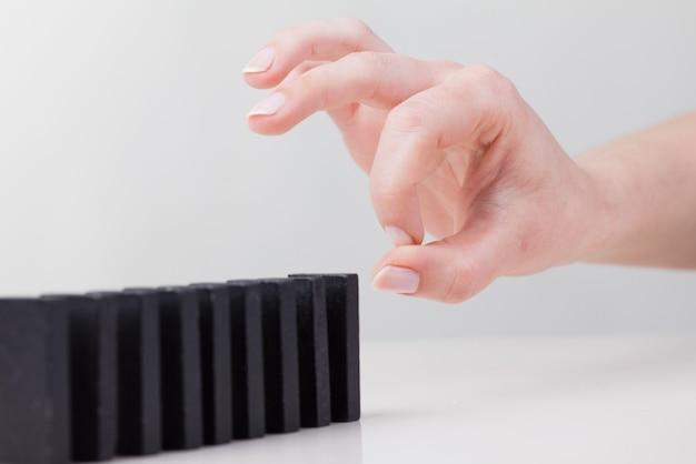 Vrouw hand omvallende dominostenen. kettingreactie bedrijfsconcept premium foto