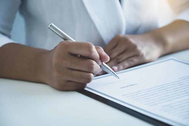 Vrouw hand ondertekenen op zakelijke contractpapieren in kantoor aan huis.