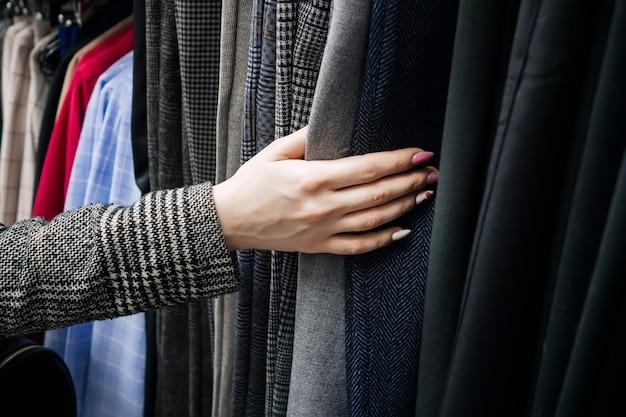 Vrouw hand op de achtergrond van een collectie van kleding in de winkel