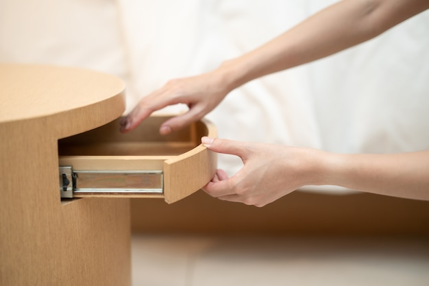 Vrouw hand openen van een lade in de houten tafel.