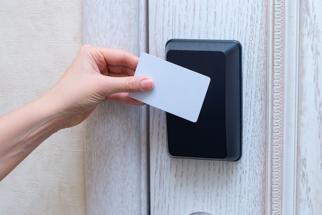 Vrouw hand openning hoteldeur met kaart