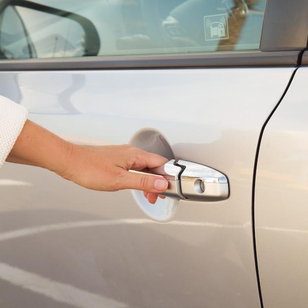Vrouw hand opent deur van grijze metalen auto close-up