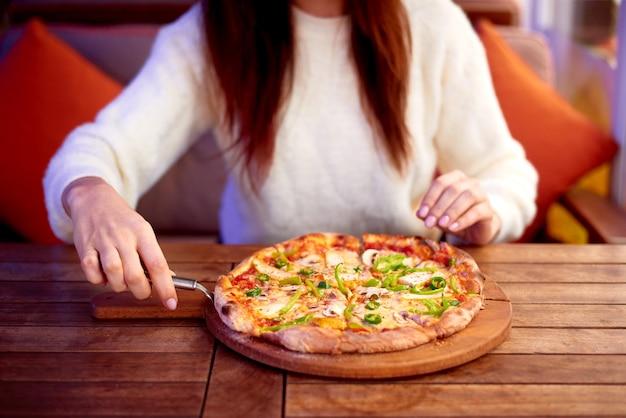 Vrouw hand plukken plakje zelfgemaakte pizza met behulp van pizzasnijder. thuis pizza eten