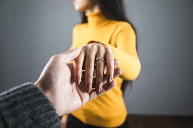 Vrouw hand ring met man hand op grijze achtergrond