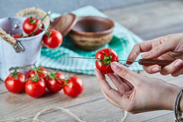 Vrouw hand rode tomaat in twee stukken snijden met mes