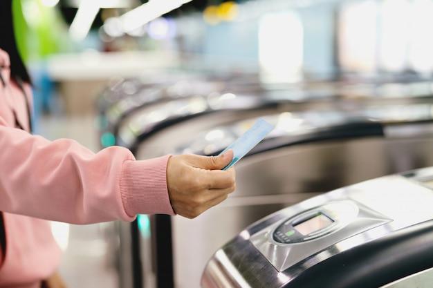 Vrouw hand scannen treinkaartje naar metro toegangspoort.