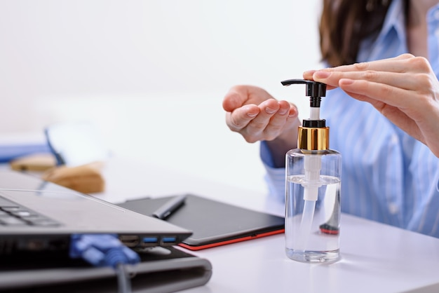 Vrouw hand schoonmaken met ontsmettingsmiddel, antibacteriële gel voor handen, externe werk op laptop thuis concept reinigen
