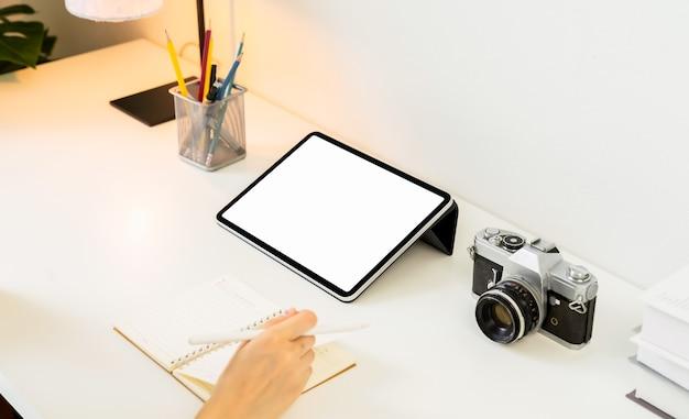 Vrouw hand schrijven op een notitieblok en een leeg wit scherm tablet en camera op tafel