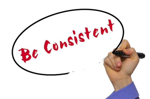Vrouw hand schrijven wees consistent op leeg transparant bord met een marker geïsoleerd op witte achtergrond. bedrijfsconcept. stock foto