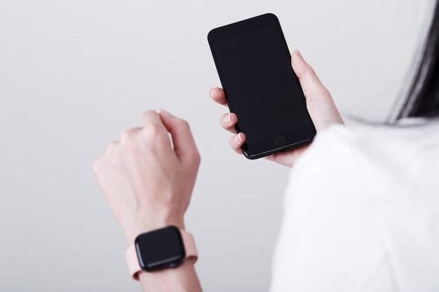 Vrouw hand slimme telefoon en slimme horloge